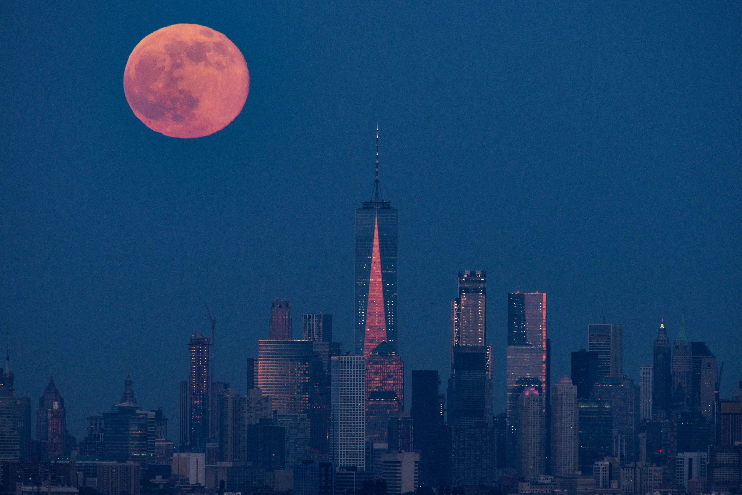 An orange moon behind the NYC skyline, centered on Freedom Tower