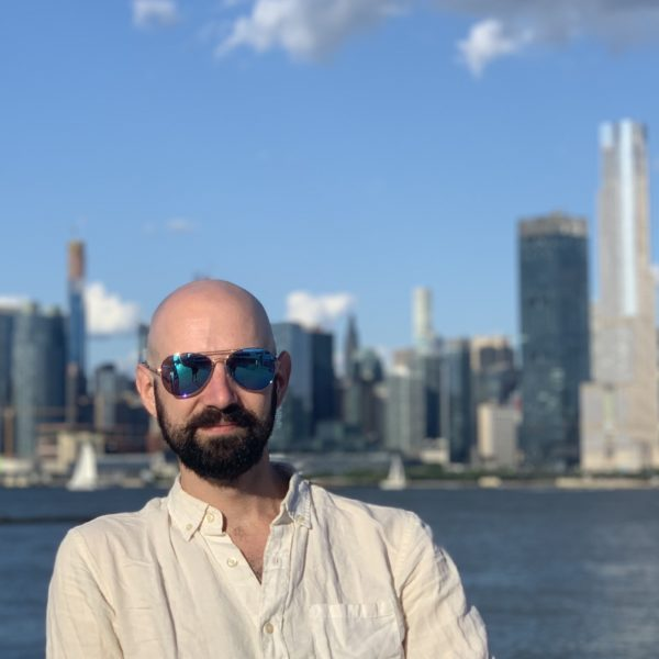 Parker in mirrored sunglasses with the NYC skyline behind him